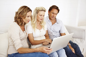 Girl with parents looking at laptop